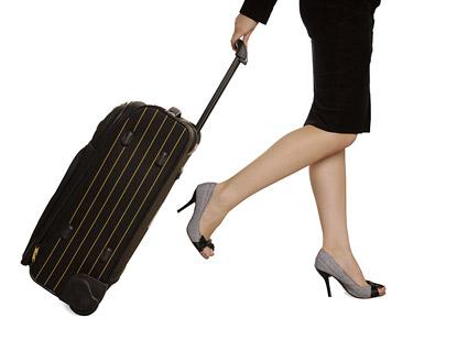 スーツケースの画像素材を手にした女性の